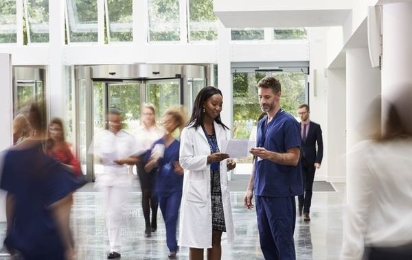 Female doctor and male nurse reviewing medical charts in the hospital while blurred out people walk by