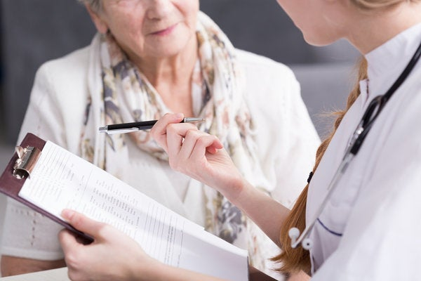 Nurse practitioner holding a clipboard and pen while talking to an elderly patient