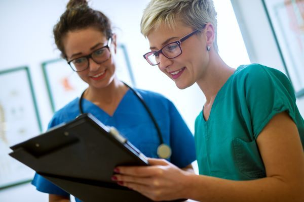 Two nurses reviewing health information on a clipboard