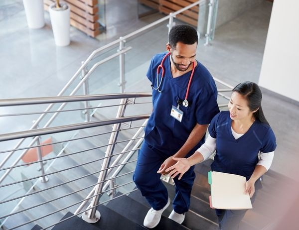 Male and female nurse walking up the stairs in a hospital while chatting