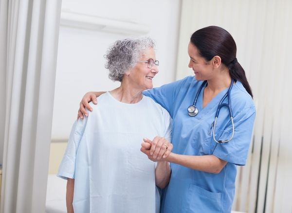 Female nurse in blue scrubs comforting a smiling elderly patient and resting her arm around her shoulders