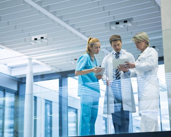 Two doctors and a nurse reviewing medical files in a hospital setting