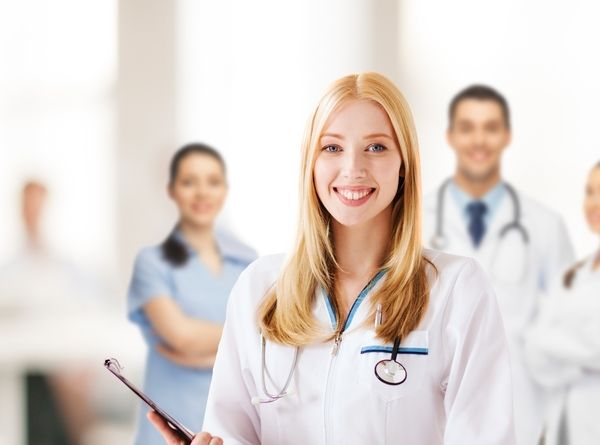 Smiling female nurse practitioner in a white lab coat with medical team behind her