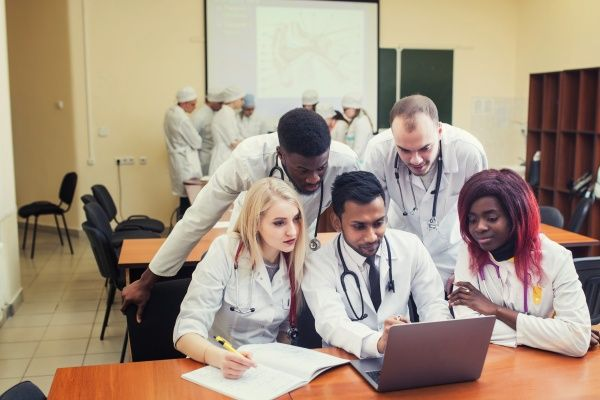 A group of culturally diverse family nurse practitioner students studying together in front of a laptop in a nursing school classroom