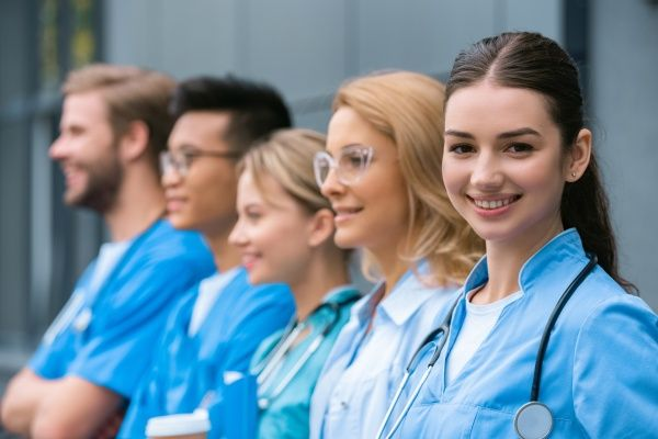 A group of nursing students standing in a row with one and smiling in an outdoor setting