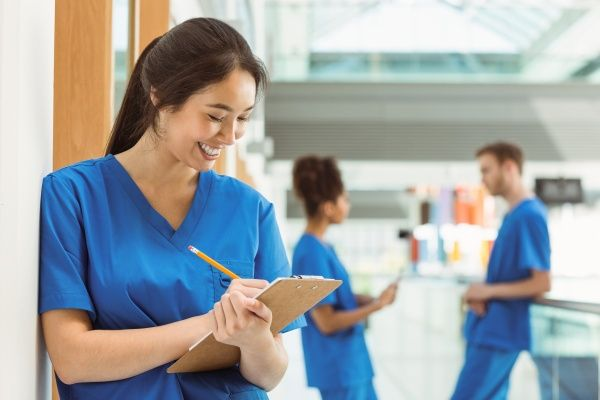 Female nurse smiling and making notes on a clipboard in a hospital setting with two other nurses conversing behind her