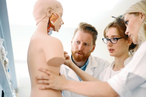 Nurse practitioner students studying a model of the human body
