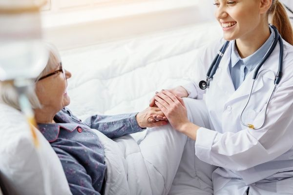 Smiling female nurse practitioner grasping the hand of an elderly female patient lying down in bed