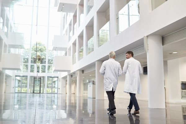 Two doctors in white lab coats walking down a modern-looking empty hospital atrium
