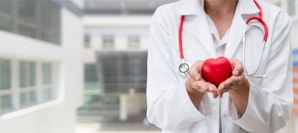 Close-up of a nurse practitioner in a white coat with a red stethoscope holding a heart in her hands
