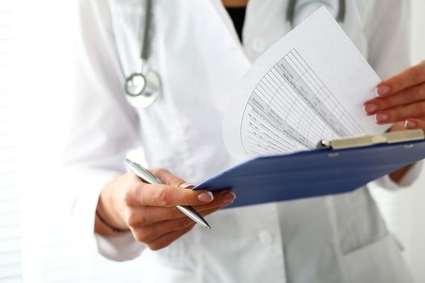 Close-up of a nurse practitioner in a white coat holding a clipboard