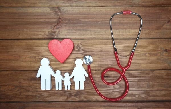 A stethoscope attached to a white cutout of a family with a heart above them