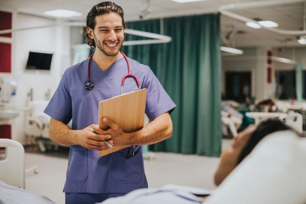 Smiling male nurse holding a clipboard and chatting with a patient