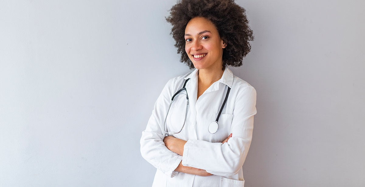 Successful nurse practitioner leaning against the wall