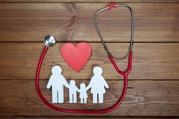White cardboard cutout of a family with a heart above them and a stethoscope against a wooden background