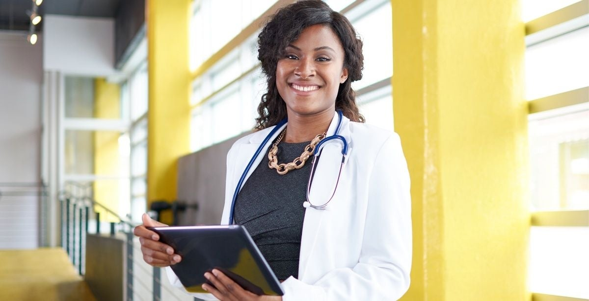Nurse practitioner in white coat smiling and holding a clipboard