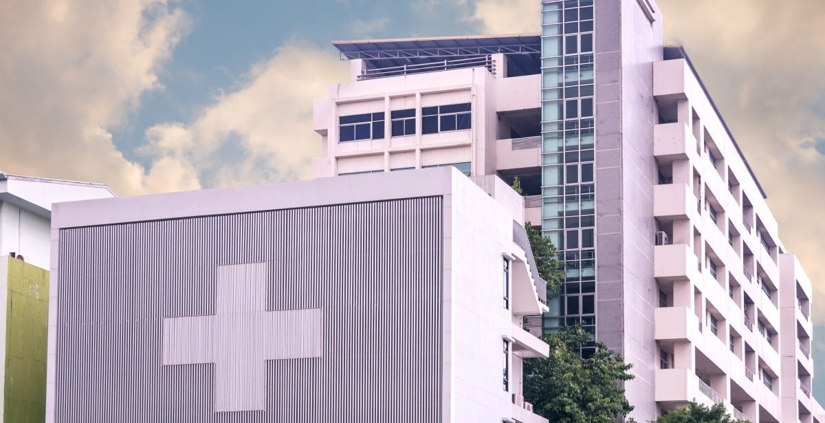Hospital with a large cross on it against a cloudy sky background