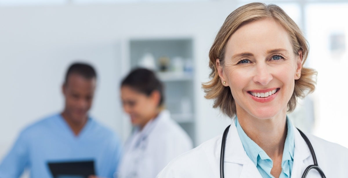 Smiling female nurse practitioner in a hospital with two registered nurses in the background