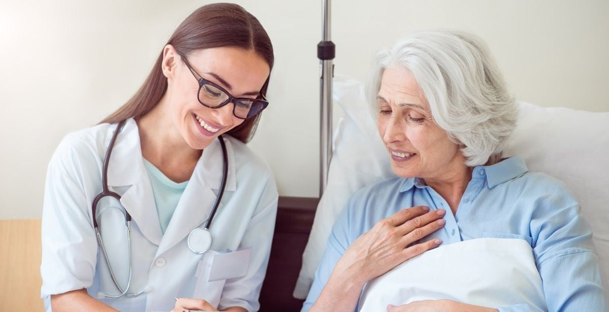 Nurse practitioner with elderly female patient in a hospital bed