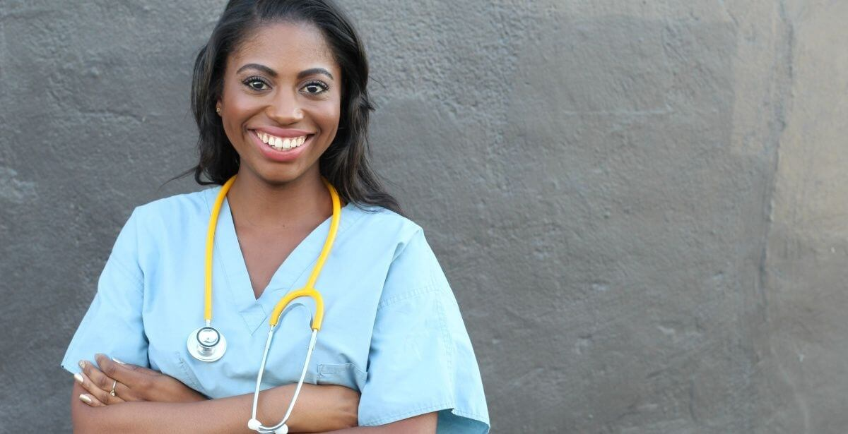 Smiling African American nurse crossing her arms against a grey wall background