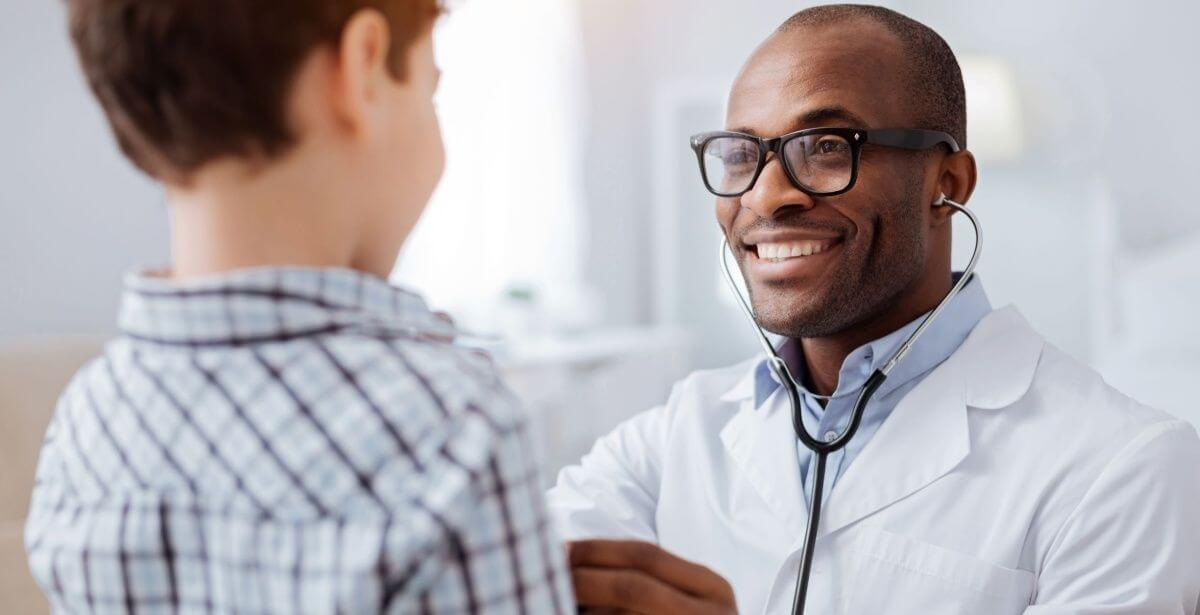 Male nurse practitioner interacting with young boy patient