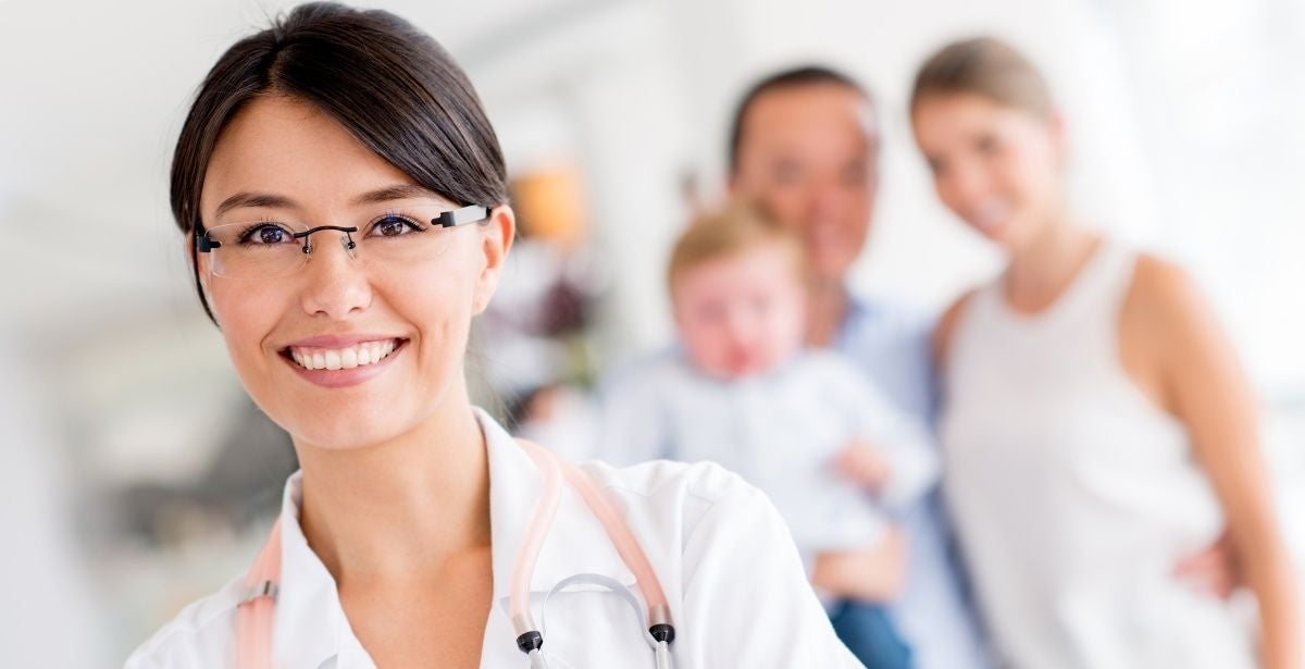 Smiling female nurse practitioner with a family standing in the background