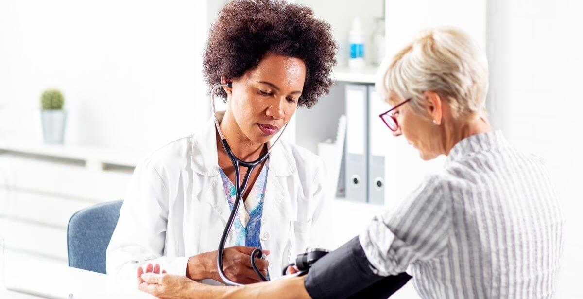 Female African American nurse practitioner taking the blood pressure of an elderly female patient