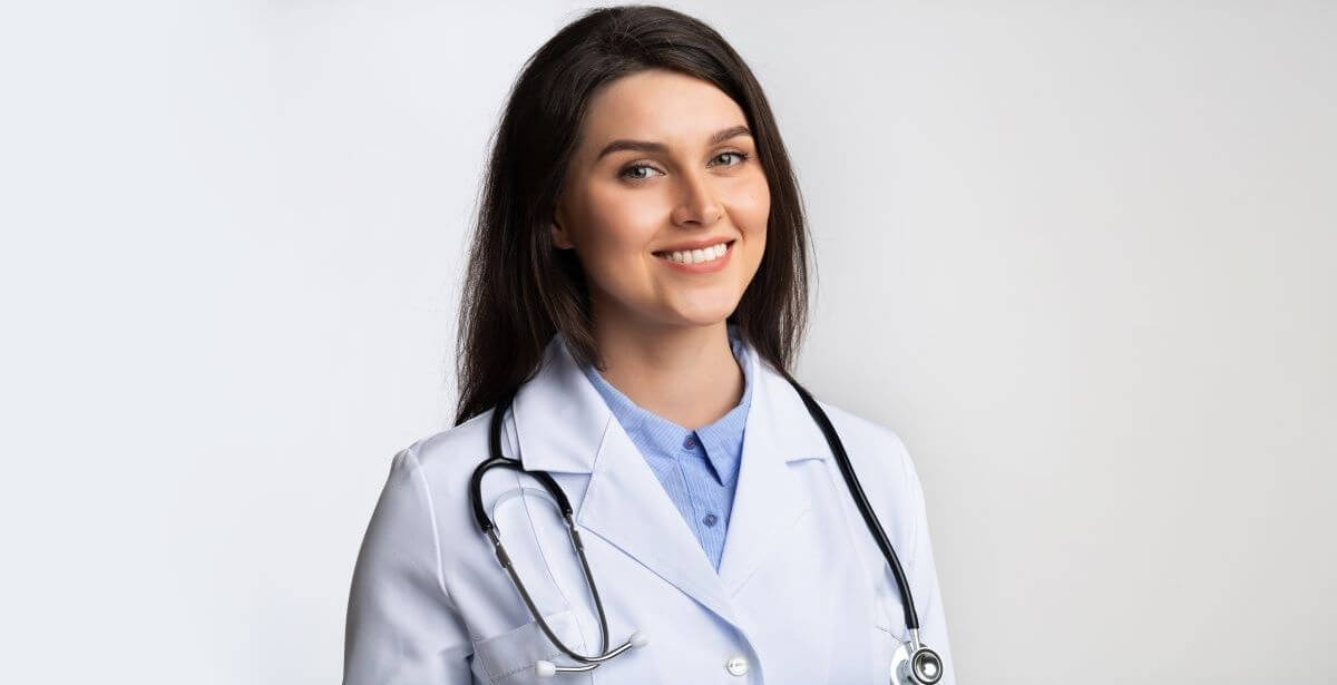Smiling female nurse practitioner against a white background