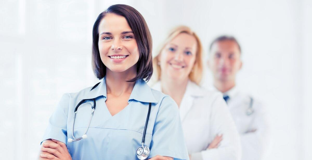 Smiling nurse practitioner with two doctors behind her