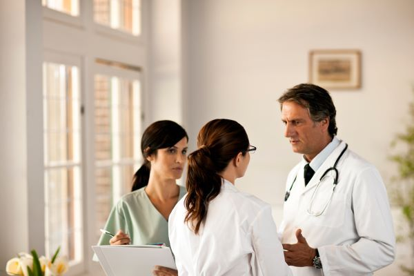 Two doctors and a nurse talking in a brightly lit room