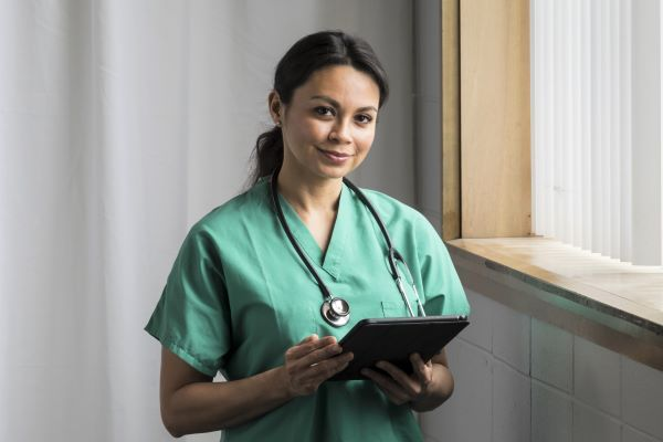 Smiling female nurse in green scrubs holding a clipboard
