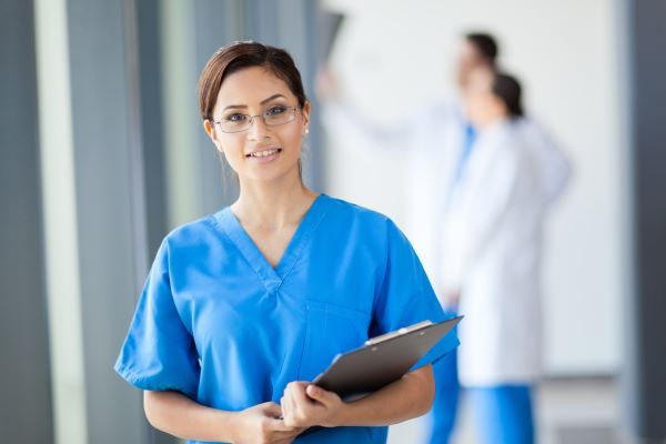 Smiling nurse wearing glasses and holding a clipboard