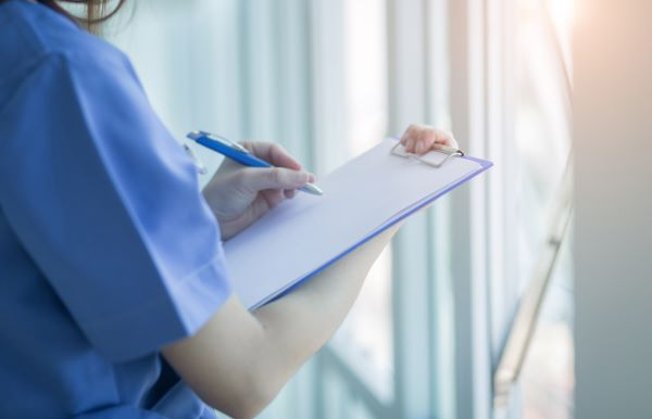 Close-up of a nurse writing on a clipboard
