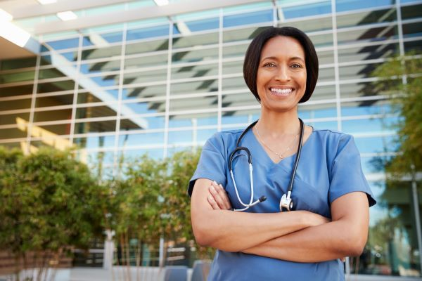 Smiling nurse standing outside of a hospital with her arms crossed