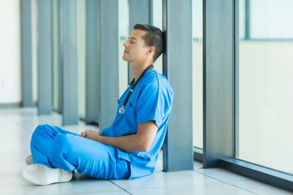 Male nurse sitting with crossed legs and performing breathing exercises