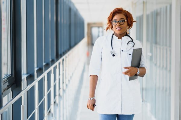 Family nurse practitioner in hospital corridor holding a clipboard